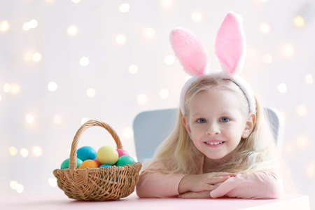 Cute funny girl with bunny ears and Easter eggs at home