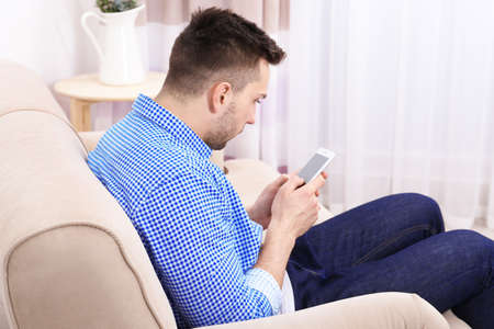 Handsome young man sitting on sofa at home. Incorrect posture concept Stok Fotoğraf - 97864411