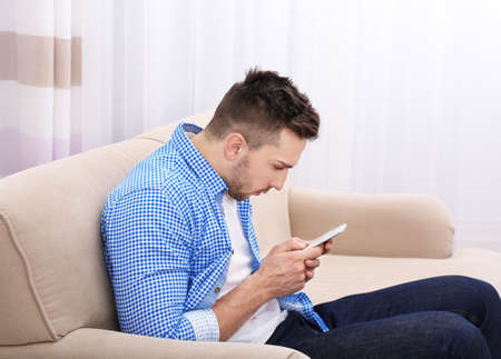 Handsome young man sitting on sofa at home. Incorrect posture concept