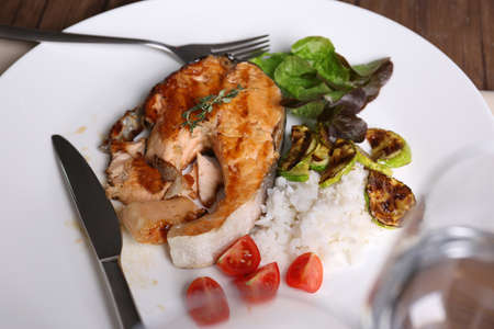 Plate with grilled salmon steak, vegetables and rice on dinning table Stock Photo