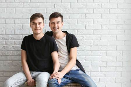 Happy gay couple sitting on white brick wall background