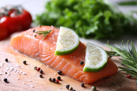 Freshly marinated salmon fillet with lime, herbs and spices on wooden cooking board Stock Photo