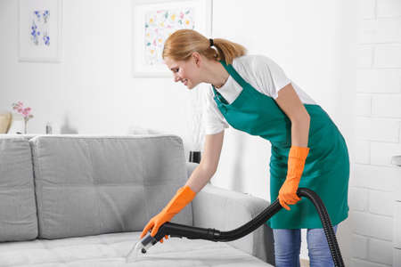 Woman cleaning couch with vacuum cleaner Stock Photo