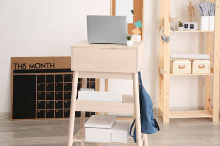 Modern stand-up desk with laptop in room Stock Photo