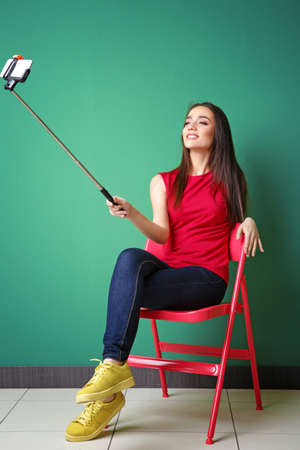 Beautiful young woman taking selfie while sitting on chair near color wall