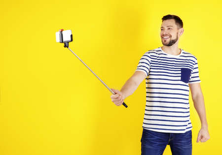 Handsome young man taking selfie on color background Stock Photo