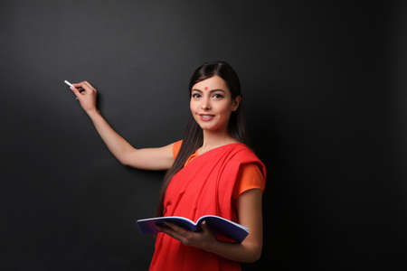 Portrait of Indian female teacher on blackboard background Stock Photo