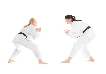 Young sporty women practicing martial arts on white background Фото со стока