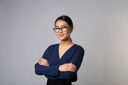 Portrait of Asian female teacher on light grey background