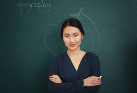 Portrait of Asian female teacher on blackboard background