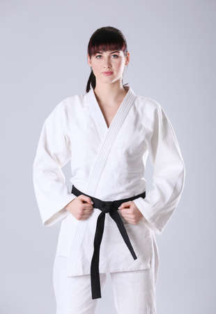 Young sporty woman in kimono on light background Banque d'images