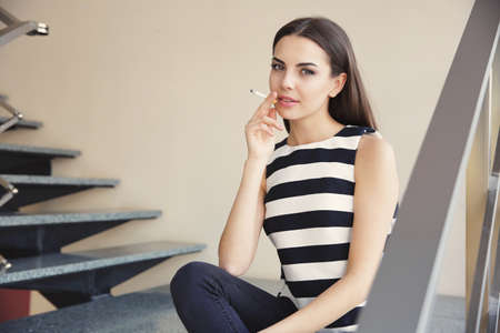 Young woman smoking cigarette on staircase