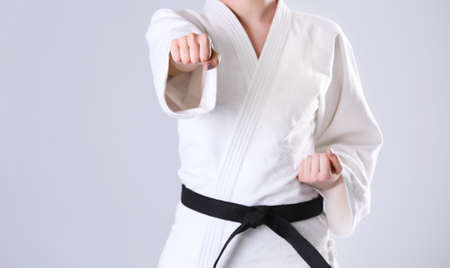 Young sporty woman in kimono on light background 版權商用圖片