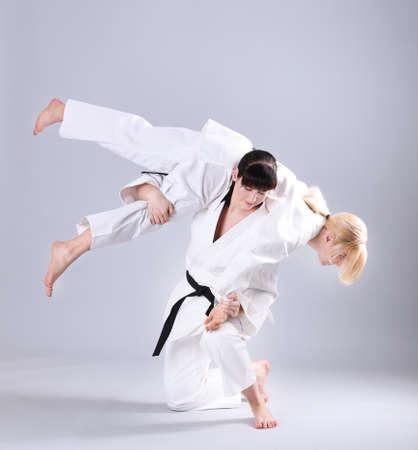 Jonge sportieve vrouwen die vechtsporten op lichte achtergrond uitoefenen