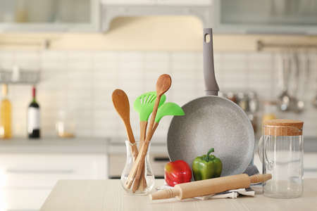 Kitchen utensils, cookware and peppers on wooden table
