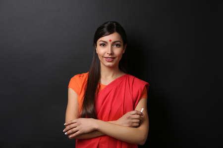 Portrait of Indian female teacher on blackboard background