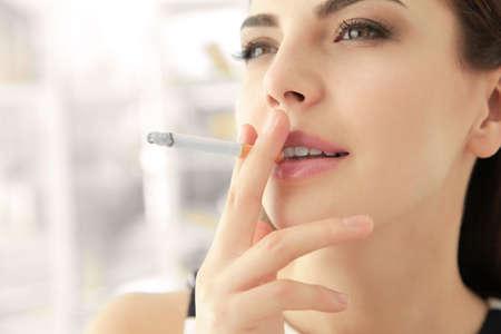 Young woman smoking cigarette at home