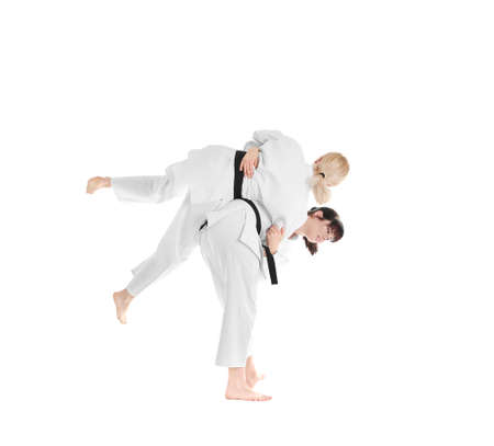 Young sporty women practicing martial arts on white background Banque d'images