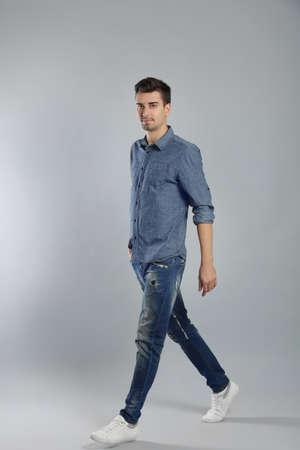 Hübscher stilvoller junger Mann, der auf grauem Hintergrund aufwirft Standard-Bild