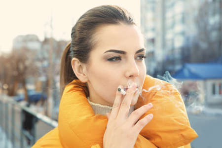 Young woman smoking cigarette, outdoor