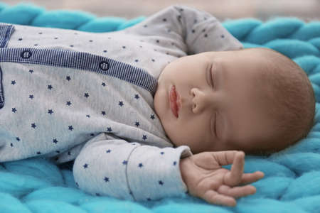 Cute little baby sleeping on plaid at home, closeup Stock Photo