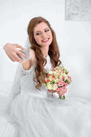 Happy bride taking selfie at home