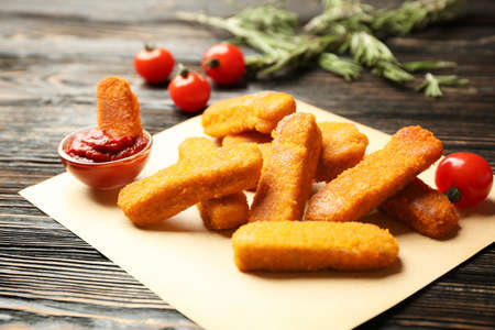 Cheese sticks and ketchup sauce on wooden background