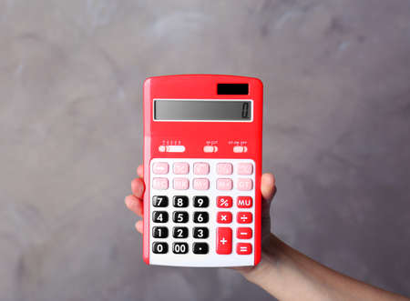 Hand holding red calculator on color background