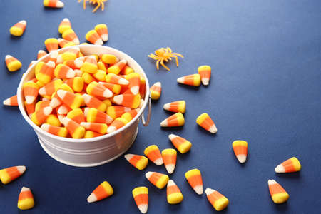 Bucket with tasty Halloween candies on color background Stock Photo