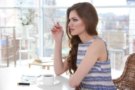 Young woman smoking in light room
