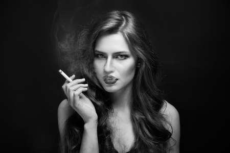 Fine art portrait of beautiful woman with cigarette on black background Stockfoto