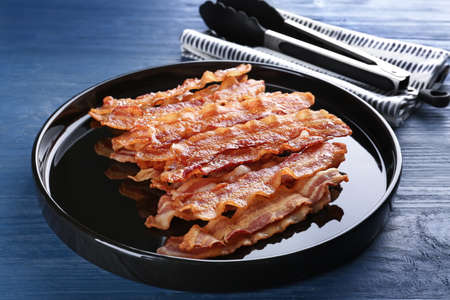 Plate with tasty bacon slices on wooden background