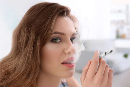 Portrait of young woman smoking in light room