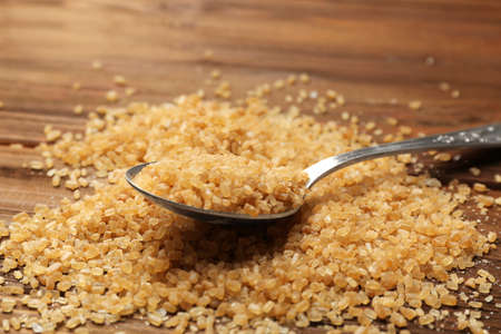 Heap of brown sugar and spoon on wooden background