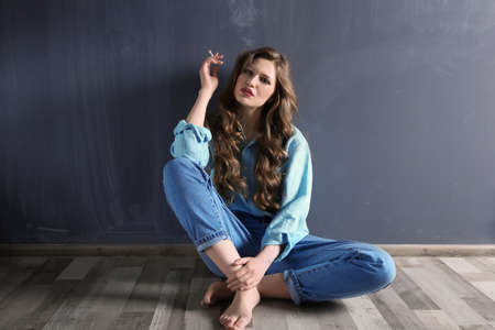 Young woman sitting on floor and smoking against color wall
