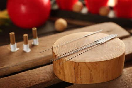 Agujas de acupuntura en tocón de madera