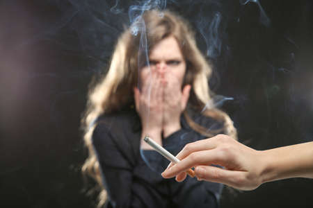 Woman covering face from cigarette smoke. Passive smoking concept Stockfoto