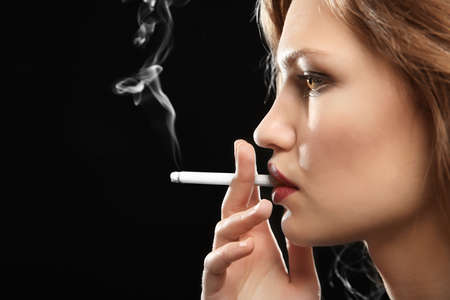 Portrait of beautiful woman with cigarette on black background