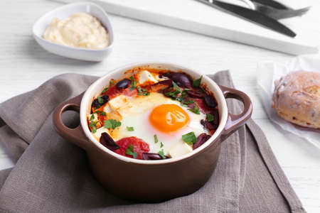 Baked egg in pot on wooden table