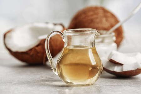 Aceite de coco fresco en cristalería en mesa gris