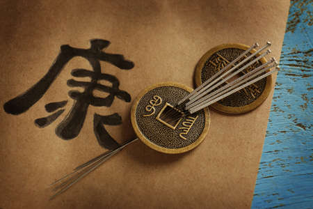 Acupuncture needles with coins on paper