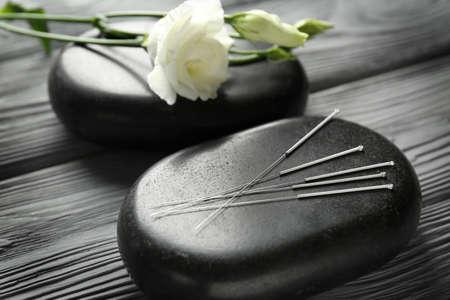 Agujas de acupuntura con piedras sobre fondo de madera% 00