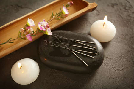 Acupuncture needles with stone and candles on textured background Foto de archivo