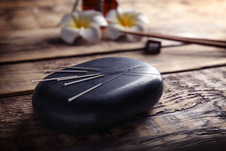 Acupuncture needles with stone on wooden background Stockfoto