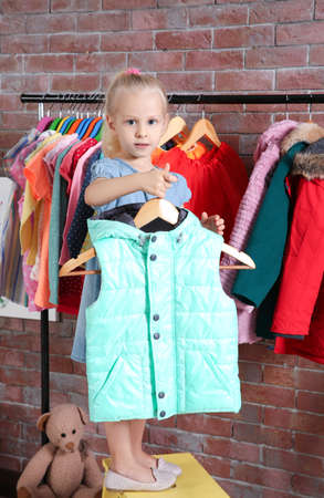 Cute little girl choosing clothes in dressing room Stock Photo