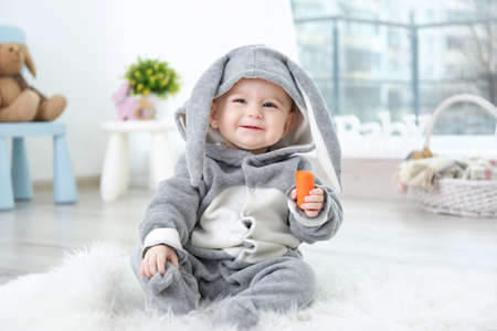 Cute little baby in bunny costume sitting on furry rug and eating carrot