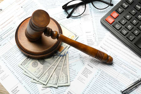 Judge gavel, money, calculator and eyeglasses on tax forms