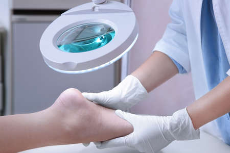 Dermatologist examining foot of patient at clinic Stock Photo