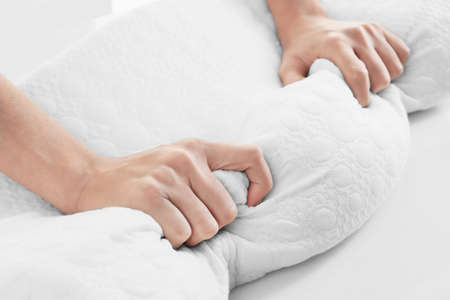 Female hands on orthopedic pillow, closeup Banque d'images