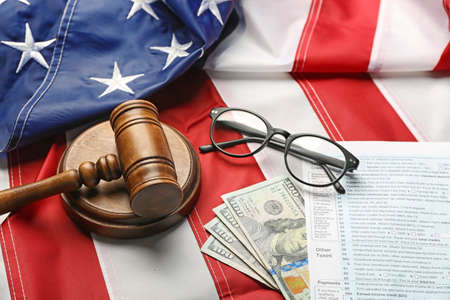 Judge gavel, eyeglasses, money and tax forms on American flag background Stock Photo